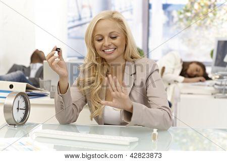 Happy blonde businesswoman sitting at desk in office looking satisfied her newly polished nails. Colleagues sleeping at background.