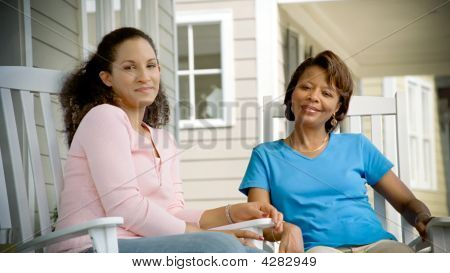 Two African American Women Relax On Porch