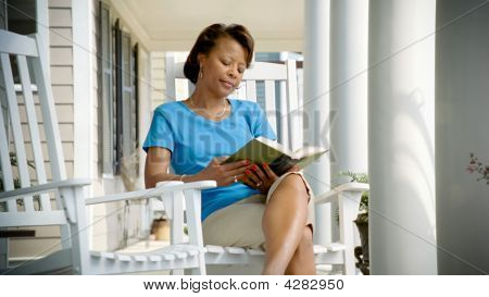 African American Woman Reads A Book On Her Porch