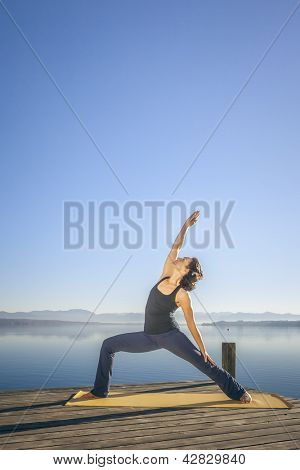 An image of a pretty woman doing yoga at the lake - Parivrtta Parshvakonasana