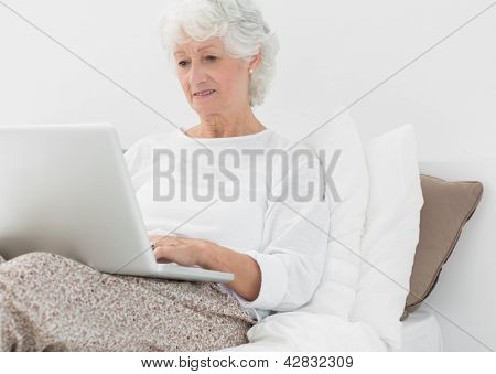 Elderly woman typing on her laptop on the bed