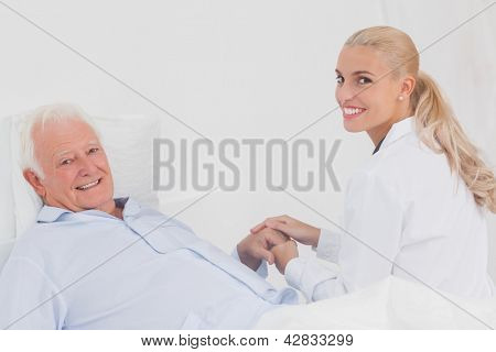 Smiling doctor holding hand of elderly patient in bed