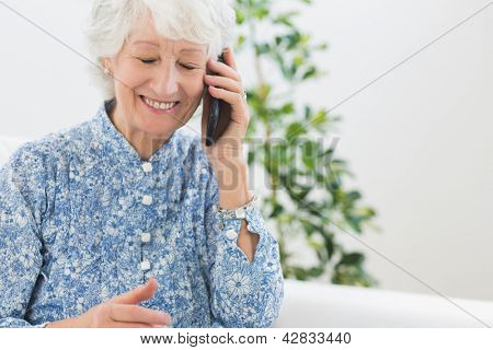 Elderly happy woman calling someone in the living room