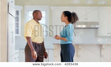 African American Couple Talk In Kitchen