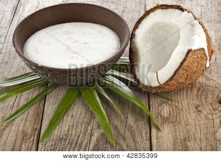 cracked coconut with milk cream in a clay bowl on wooden table