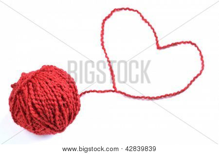 Red yarn or string heart away from rolled ball