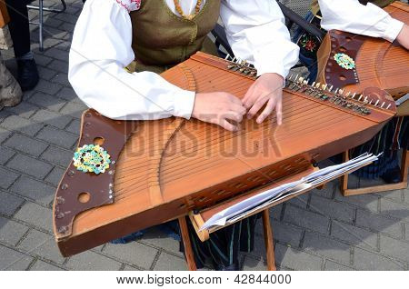 Girl Playing With Ethnographic String Musical Instrument