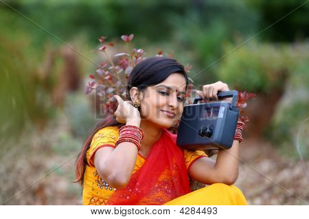 An Asian Rural Woman Listening To Radio