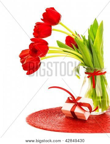 Photo of beautiful red fresh tulips flowers in glass vase, white gift box with red ribbon bow on the table in studio, romantic still life isolated on white background, happy mothers day, love concept