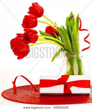 Image of beautiful red fresh tulips flowers in glass vase, white gift box with red ribbon bow on the table in studio, romantic still life isolated on white background, happy mothers day, love concept