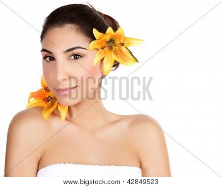 Photo of beautiful arabic woman with yellow lily flower in head, portrait of cute brunette girl wearing bath towel isolated on white background, natural facial cosmetics, beauty and spa concept
