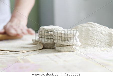 Woman with a rolling for Karelian pies