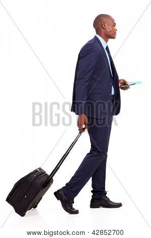 african american businessman walking with trolley bag on white