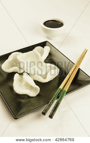 Traditional chinese snack, prawn crackers on black plate