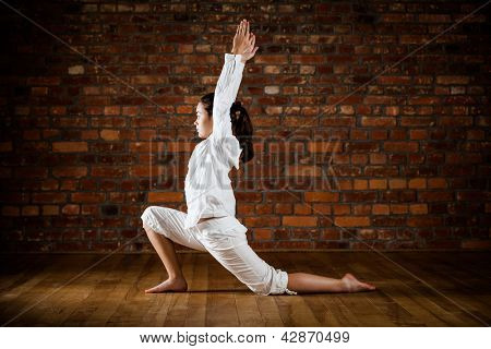Girl exercising yoga against brick wall