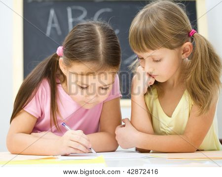 Cute little girls are writing using a pen in preschool
