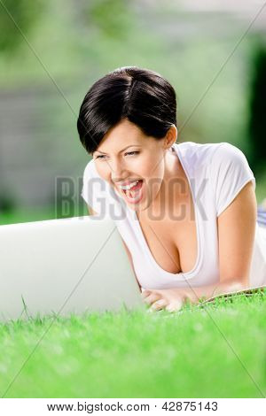 Woman lying on the green grass works at the silver laptop. Concept of the online communication