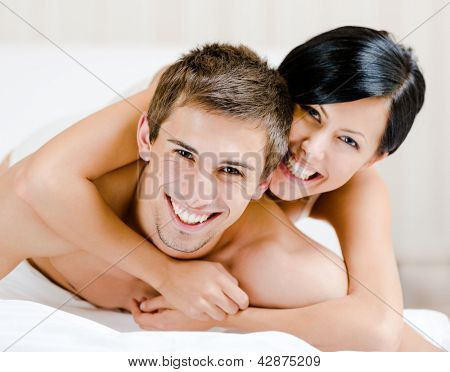 Close up of laughing couple who plays in bed. Woman lying on the back of the man  embraces him