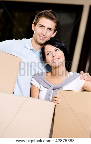 Happy couple carrying cardboard containers while moving to new house