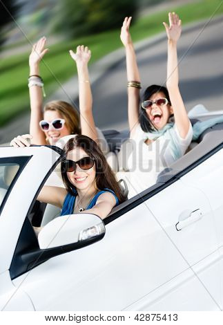 Group of happy teenagers driving the cabriolet. Adorable cabriolet trip on vacation
