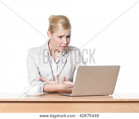 Attractive business woman sitting at a desk with laptop, isolated