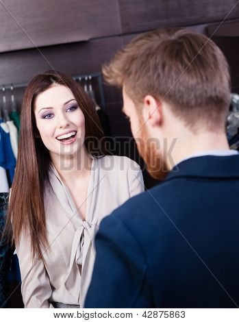 Young beautiful woman talks to shop assistant