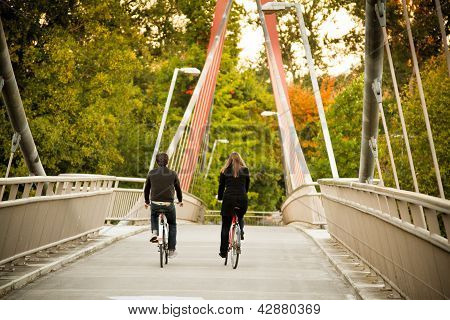 Couple Cycling On Bridge