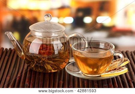 Exotic green tea with flowers in glass teapot on bright background