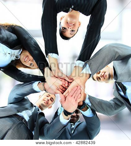 Small group of business people joining hands, low angle view.