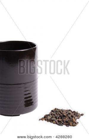 Black Cup Heap Of Green Tea Leaves