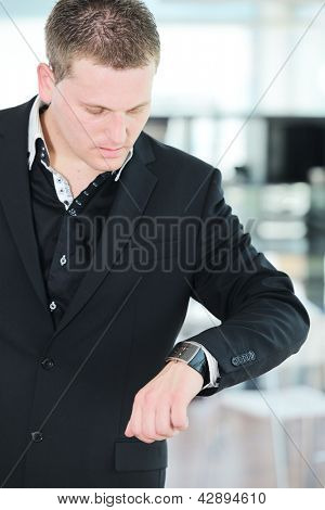 Businessman looking at clock wristwatch on hand in office