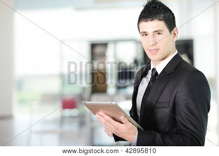 Portrait of a young successful businessman using tablet computer at office