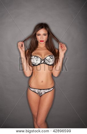 Hot young woman in black and white lingerie posing on grey background