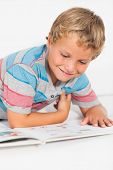 picture of storybook  - Happy boy reading a storybook lying on the floor - JPG