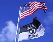 BROOKLYN, NEW YORK - MARCH 3: Brooklyn Nets and American flags flying in front of  Barclays center
