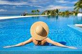 image of sunbathing woman  - Woman in hat relaxing at the pool - JPG