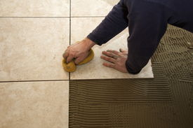 pic of mortar-joint  - A man on his knees installing a ceramic tile floor - JPG