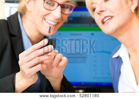 Older woman or female pensioner with a hearing problem make a hearing test, the accoustician holding a model of a hearing aid
