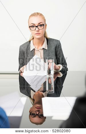 Job applicant during her interview, with her resume in front of her