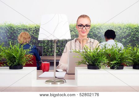 Portrait of smiling business woman working in a green office, sitting at a hot desk, with two others in adjacent seats