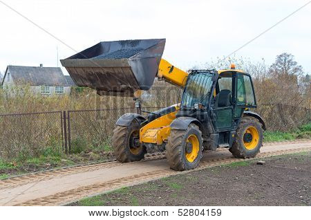 Front Loader In Action. The Hoist Raised.