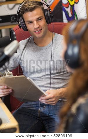Attractive happy radio host interviewing a guest holding clipboard in studio at college