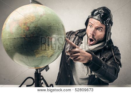 amazed aviator indicates a country on the globe
