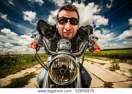 Funny Biker in sunglasses and leather jacket racing on the road (fisheye lens)