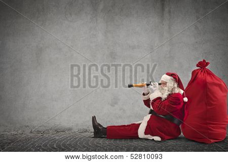 Santa Claus sitting on the floor looking through spyglass