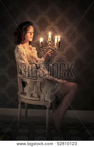 beautiful woman sitting in the living room with ancient candelabrum in hand