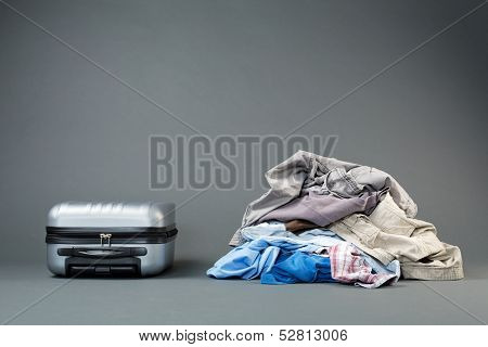 Pile Of Clothes And A Suitcase