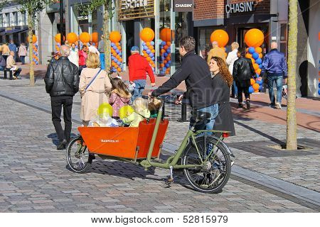 Young Parents Carry Children In The Bicycle Stroller By Celebratory Street  In Dordrecht, Netherland