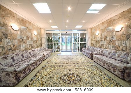 Spacious light hall with sofas at the walls of a holiday home