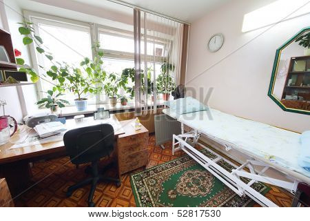 Interior of a light doctors consulting room with a bed and a workplace
